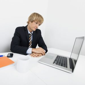 Bored mid adult businessman with laptop at desk in office